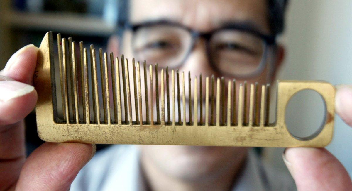 16. 63-летний изобретатель Хань Юйцзы держит одно из своих творений — расческу, которая также служит
