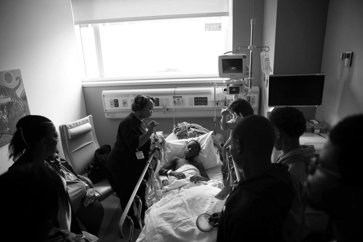 Семья мальчика и сотрудники больницы у кровати Тэйвона.