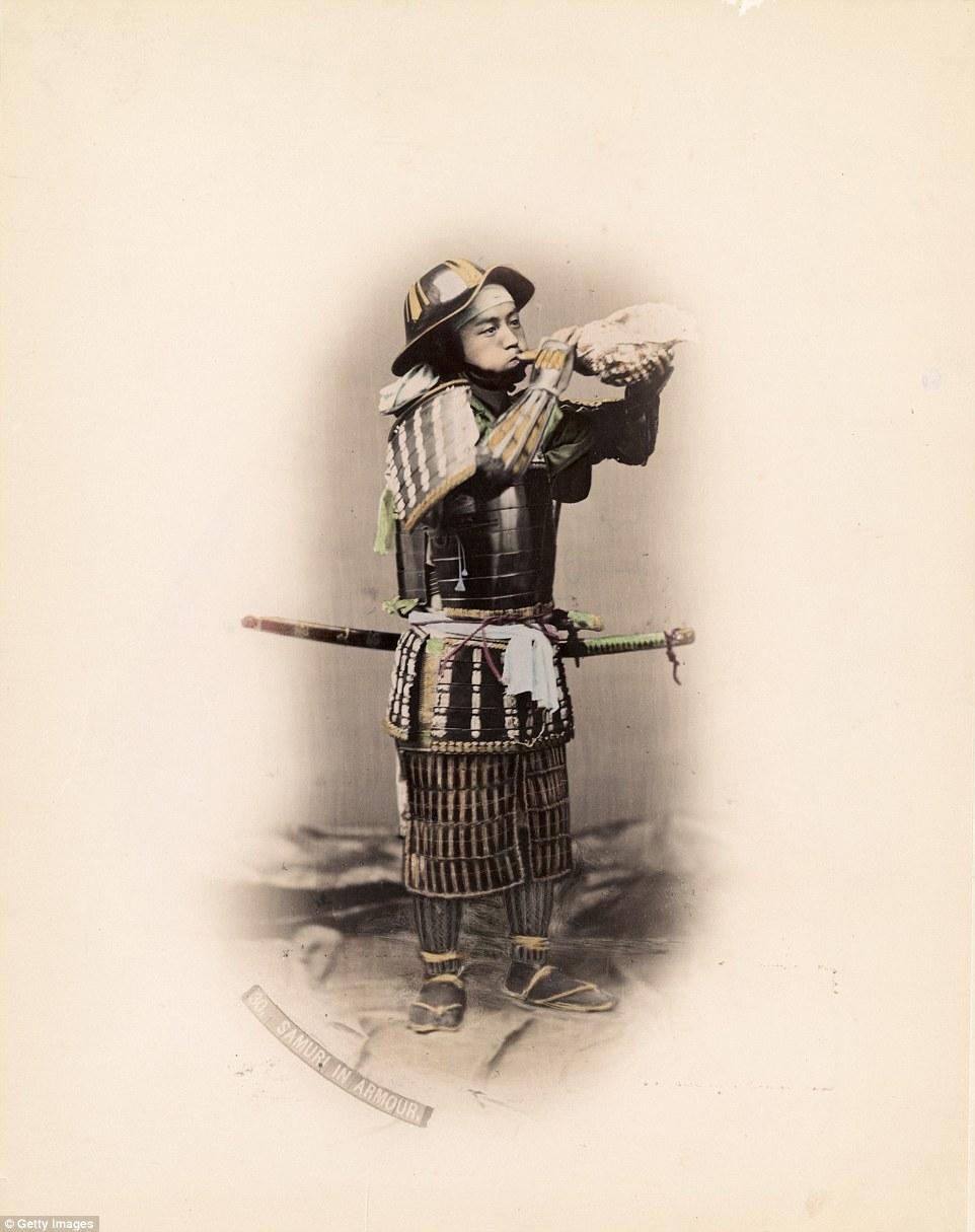 Самурай в традиционном наряде и обуви дует в морскую раковину.