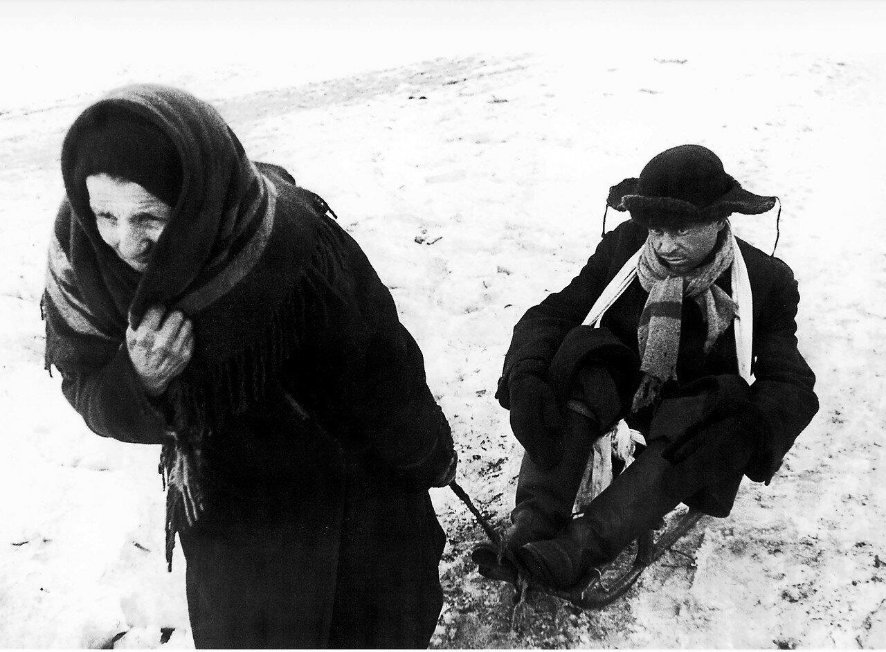 1942,7 февраля. Пожилая ленинградка везет на санках мужчину-дистрофика.
