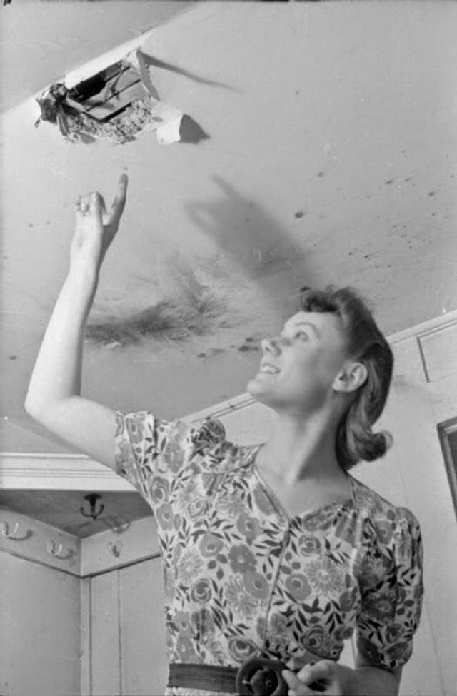 10. Оливия указывает на отверстие в потолке, след от недавно упавшей бомбы. На потолке можно увидеть подпалины возле отверстия