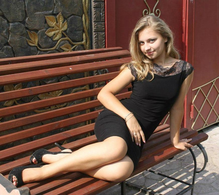 Милая блондинка на скамейке в платье