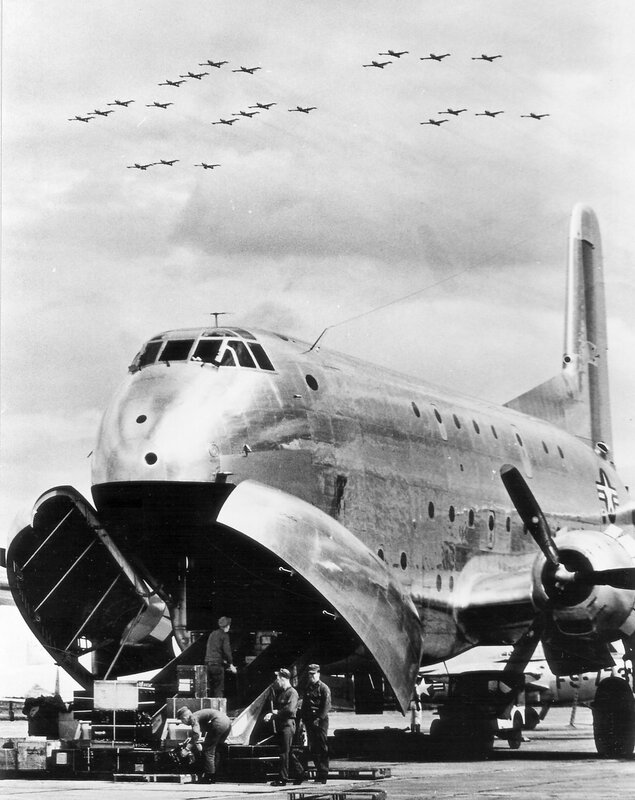 """F-84G """"Thunderjets"""" of the 27th Fighter Escort Wing, above C-124s"""