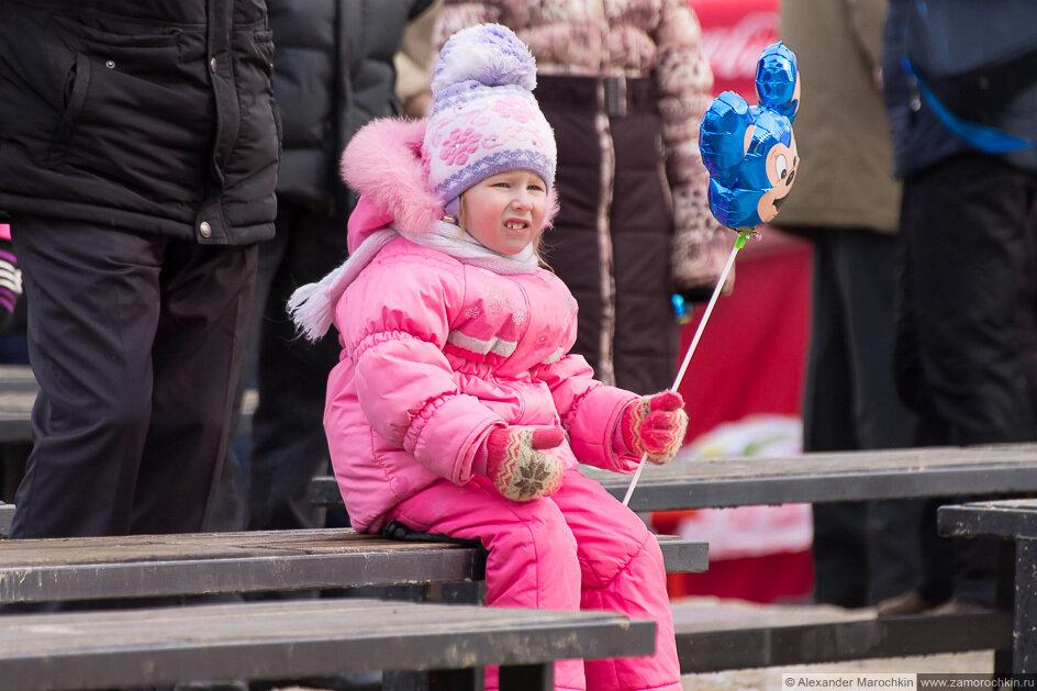 Девочка с шариком в руках сидит на скамейке
