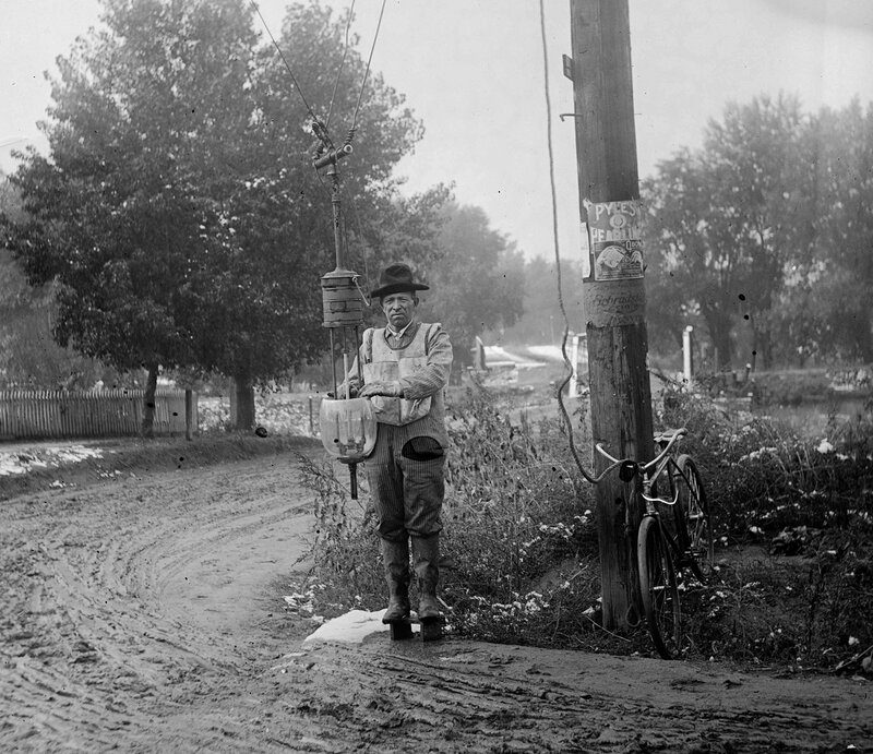 An arc-light trimmer poses with a lowered arc lamp on Alameda Avenue in Denver, Colorado, between 1911 and 1923