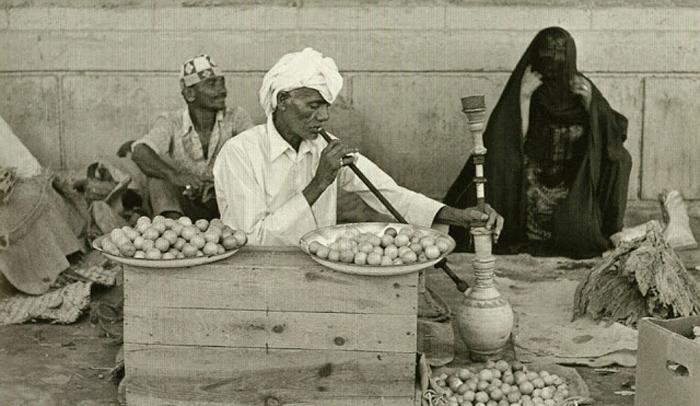 Мужчина, курящий кальян, продает лимоны и сушеные травы.