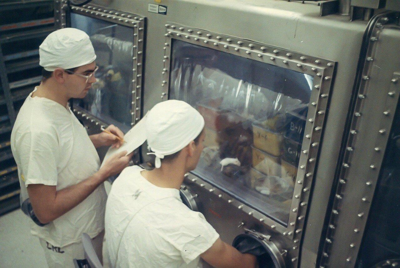 Далее их ополоснули стерильной водой и просушили азотом, после чего через вакуумный шлюз они были помещены в вакуумную зону. На снимке: Ученые изучают лунные образцы в лунной лаборатории