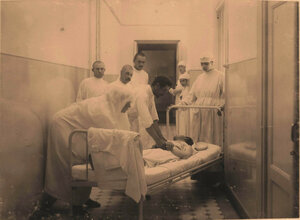 Медицинский персонал за перевозкой оперированного больного из операционной в палату.