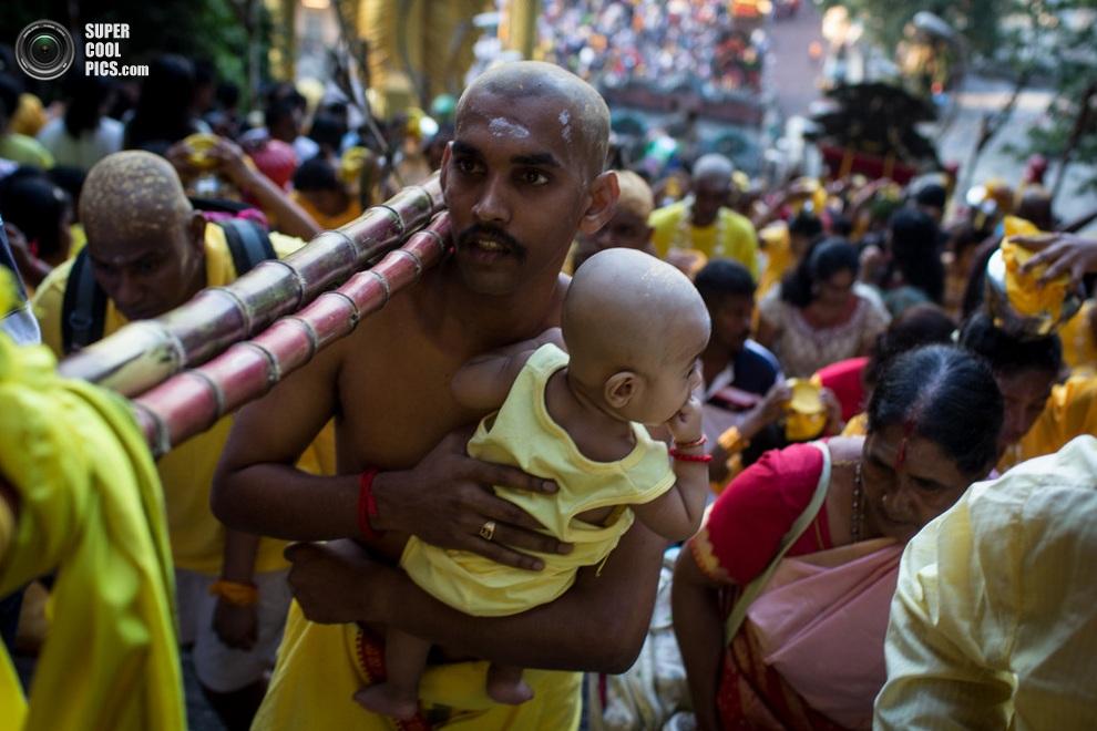 Тамильский мужчина с ребёнком проходит 272 ступени к священным пещерам Бату, Куала-Лумпур, Малай