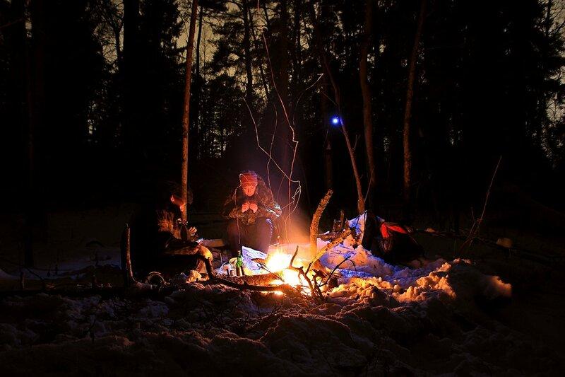 Привал у костра в зимнем лесу: огонь, освещающий небольшую полянку, нехитрая снедь и свет фонариков среди сосен