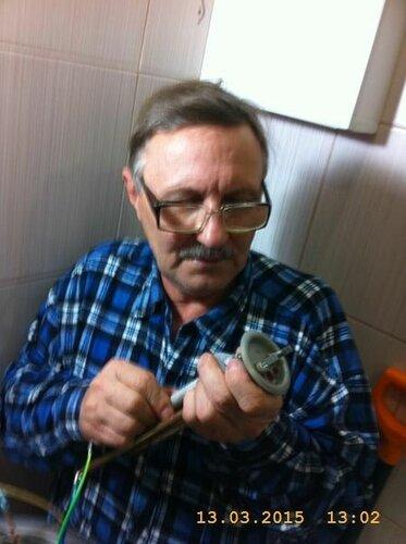 Сантехник вкручивает новый анод
