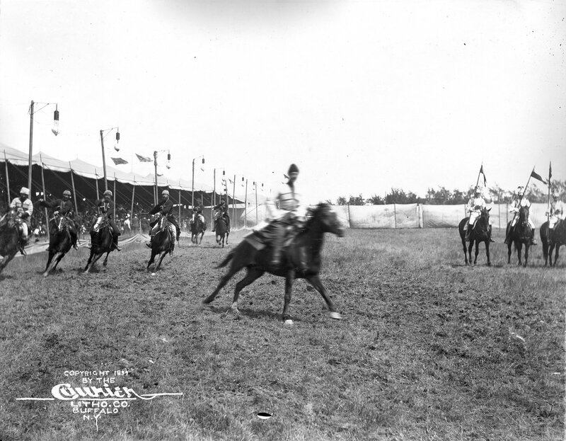 A group of Russian Georgian Cossacks ride horses through a grassy area during a performance of Buffalo Bill's Wild West Show. David Kadjaia, rides in the center midground slightly in front of the rest of the group.1899