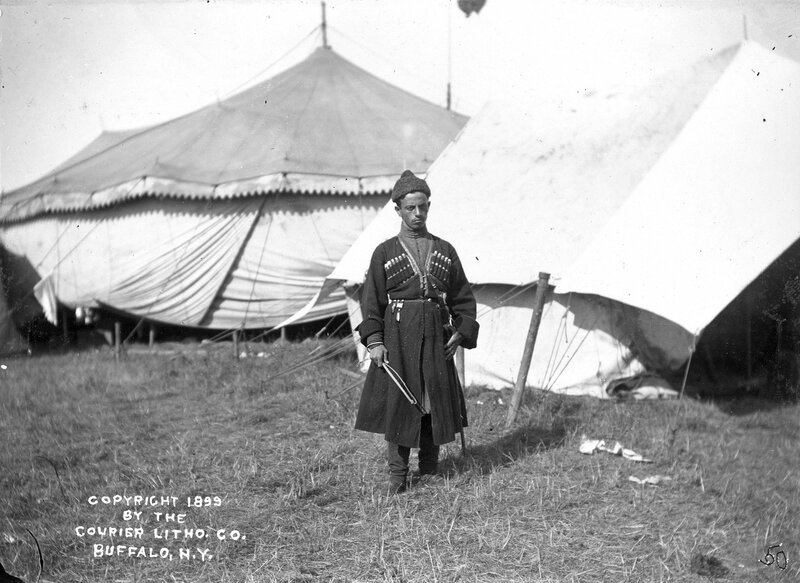 Russian Cossack (Georgian), Ivane Baramidze, stands in front of a tent in a camp for Buffalo Bill's Wild West Show,1899