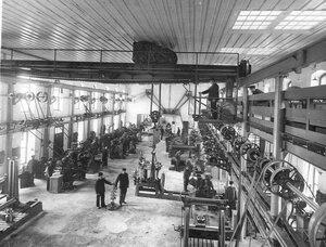 Рабочие за изготовлением радиоаппаратуры в большом цехе завода.