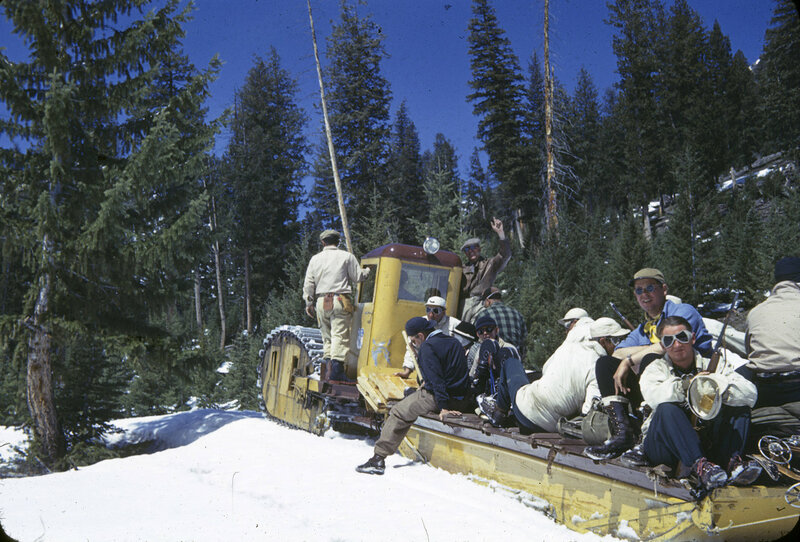 1942. Arnold Faucus (foreground) w / film crew a one track snowcat, steered with skis from behind the cab