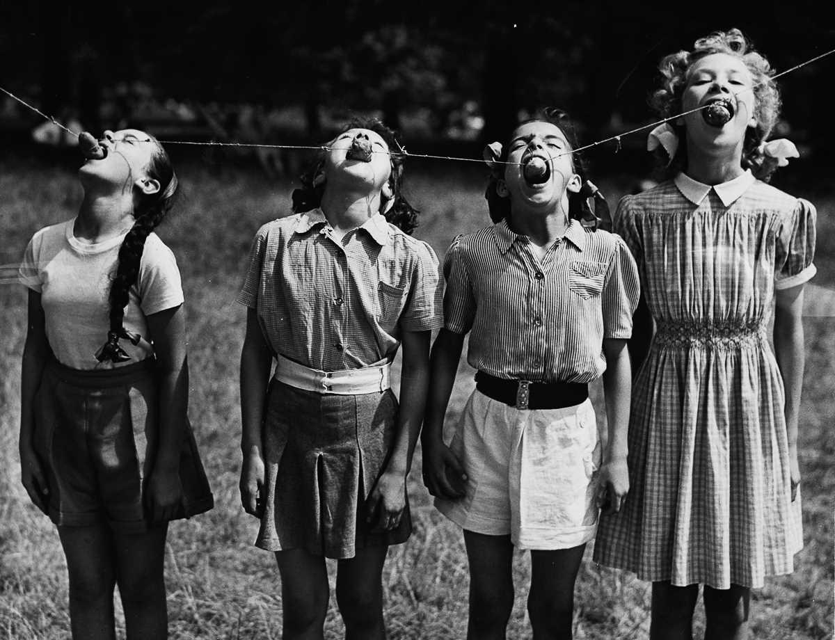 12. 25 июля 1952 года. Лондонские учащиеся пытаются съесть подвешенный картофель.