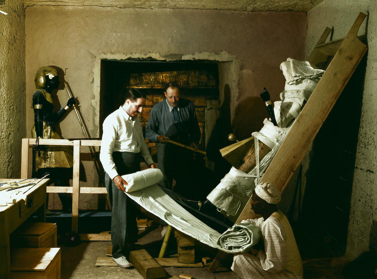 Говард Картер, Артур Каллендер и египетский рабочий заворачивают одну из дозорных статуй для транспо
