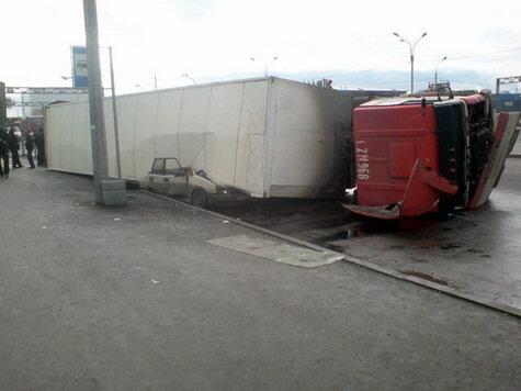 Огромная фура завалилась на припаркованную машину