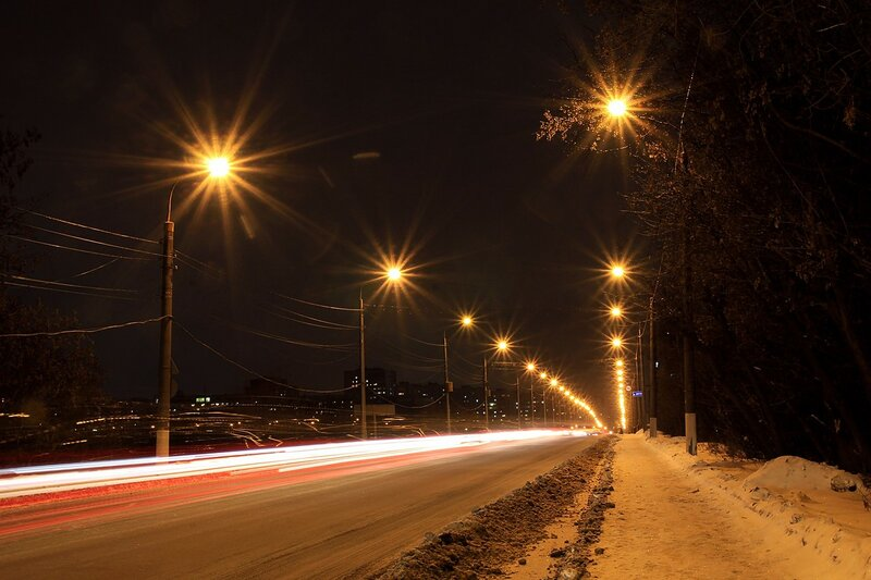 Огни фонарей с лучами и треки от фар машин на старом мосту через Вятку зимней ночью