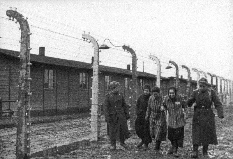 Советские офицеры и освобожденные узницы Освенцима идут вдоль бараков
