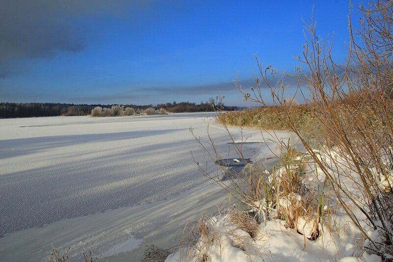 Зимний пейзаж озера Жуково (Кирово-Чепецк): покрытая льдом гладь озера, проталины у берега, торчащая из снега засохшая трава