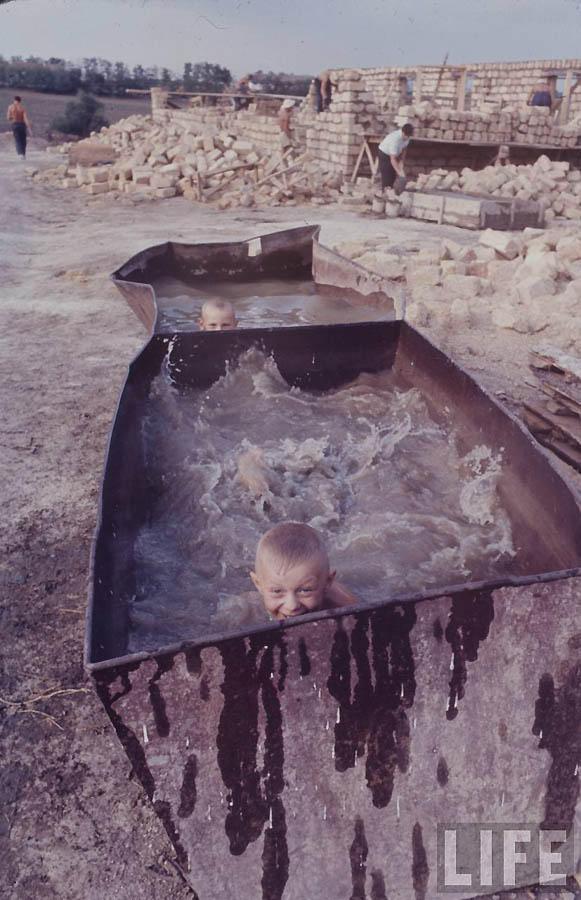 Радостные дети купаются в импровизированном бассейне.