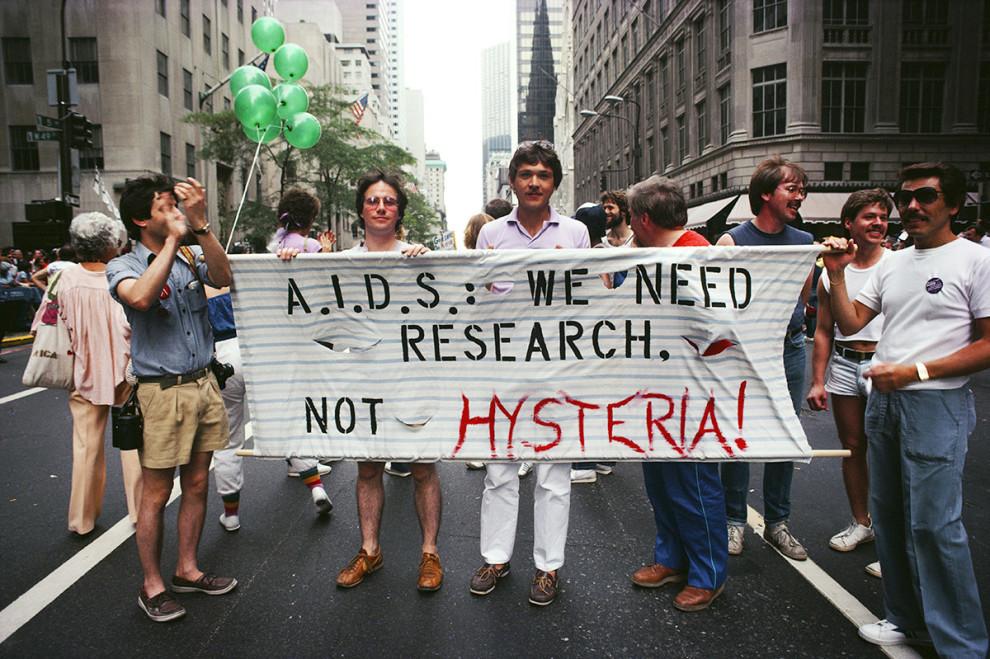 Гей-парад на улицах Нью-Йорка в июне 1983 года. Плакат марширующих гласит: «СПИД: нам нужны исследов