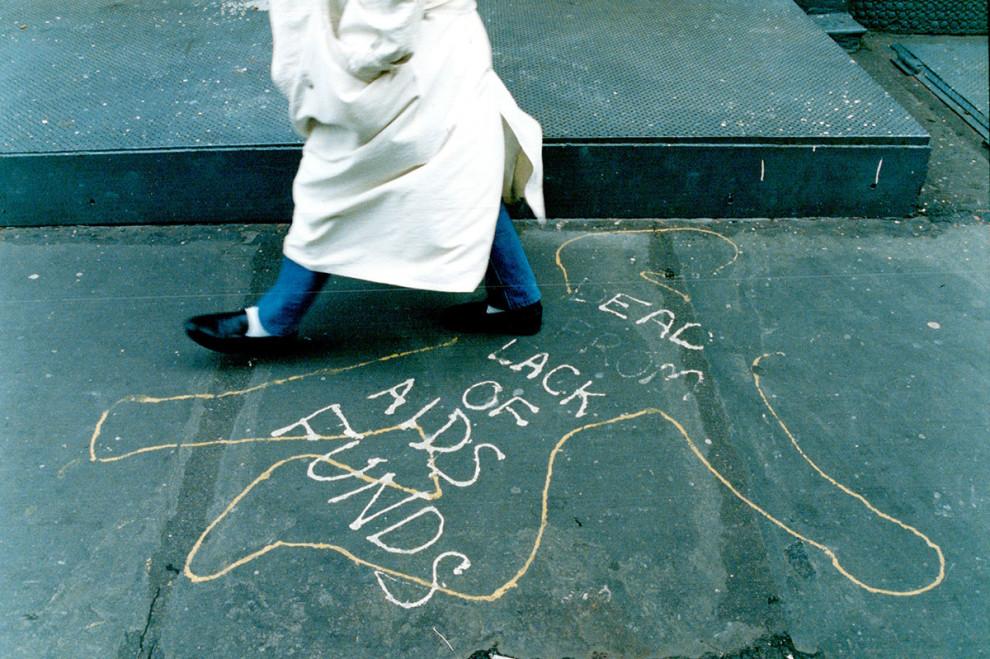 Женщина проходит мимо граффити в Нью-Йорке, которое гласит: «Мертв из-за недостаточного финансирован