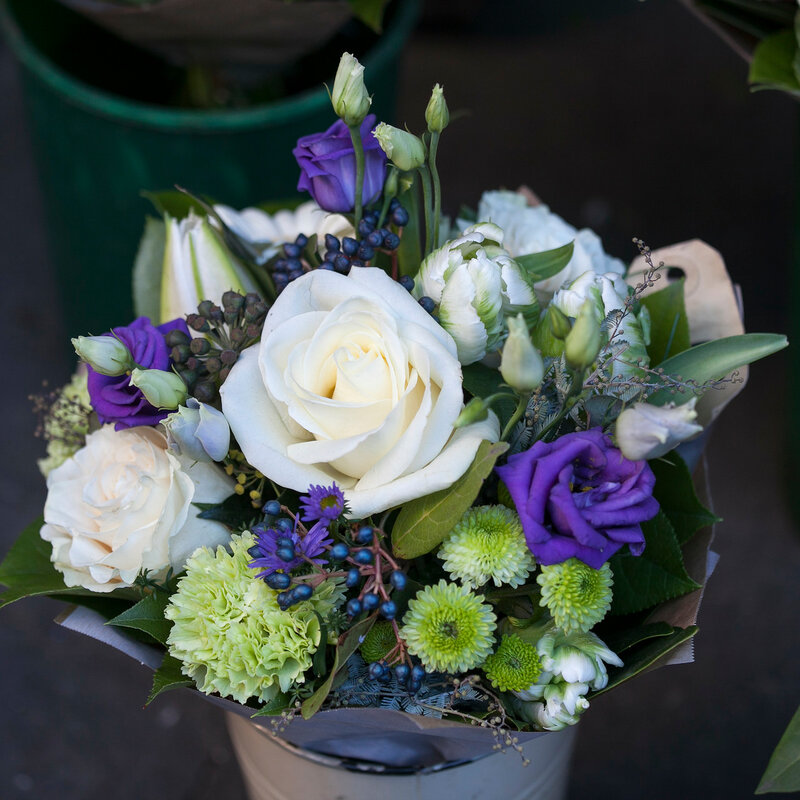 bouquet of white and blue roses with lisianthus and chrysanthemum in an aluminum bucket