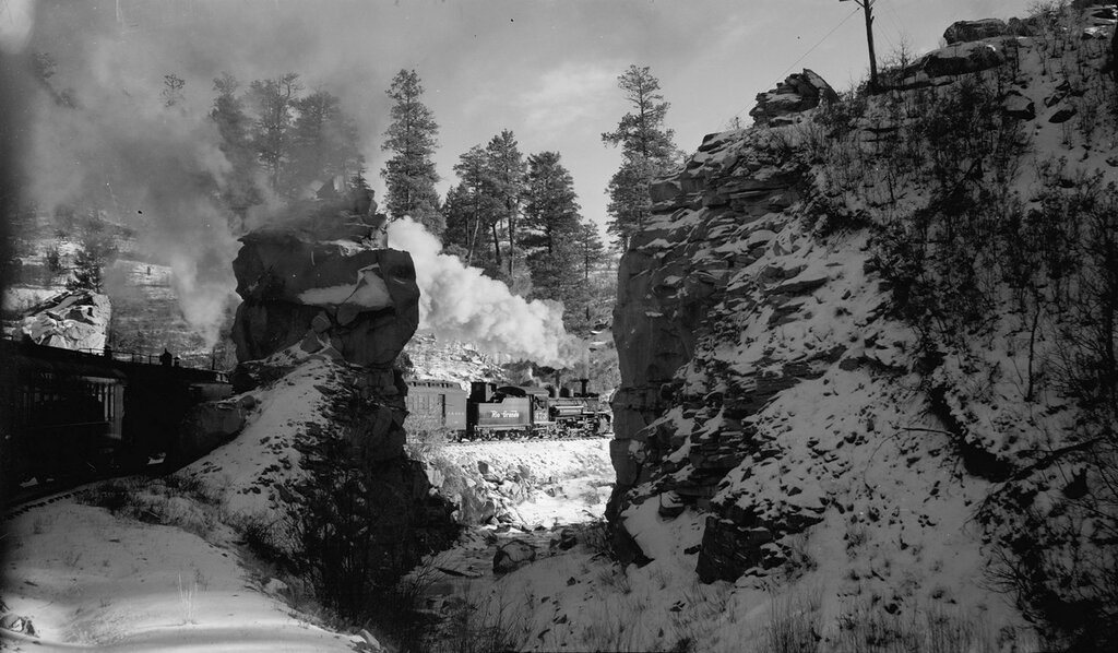 Denver and Rio Grande Western Railroad locomotive 473 and coaches pass by rocky crags somewhere between Alamosa and Durango, Colorado. December 25, 1948.