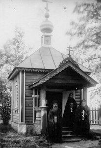 Схимники и священник выходят из часовни.