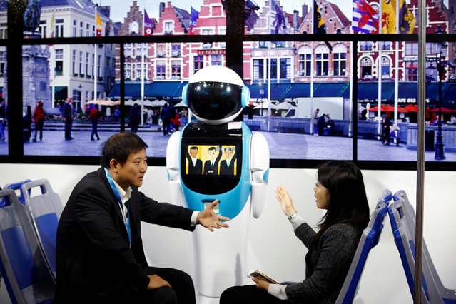 People talk as they sit in front of a robot in a public transport simulator at the WRC 2016 World Ro