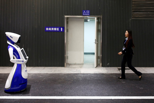 A woman walks past a robot by Robot4U Tech at the WRC 2016 World Robot Conference in Beijing, China,