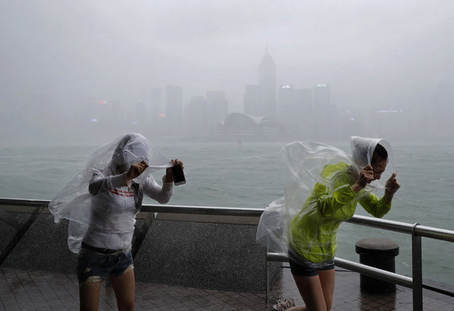 People brave the wind on the waterfront of Victoria Habour as Typhoon Haima approaches Hong Kong, Fr