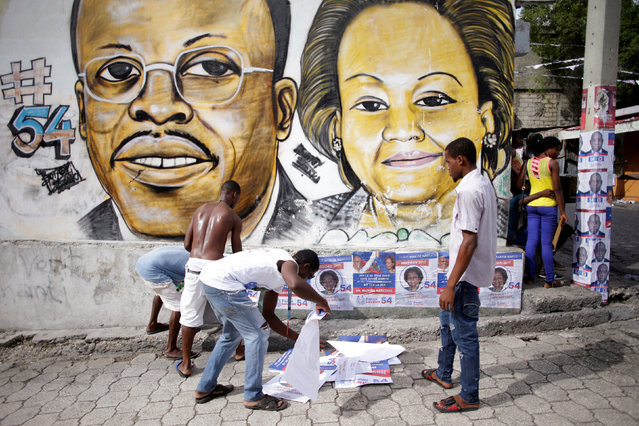 Supporters of Fanmi Lavalas political party plaster electoral posters below a painting of ousted dep