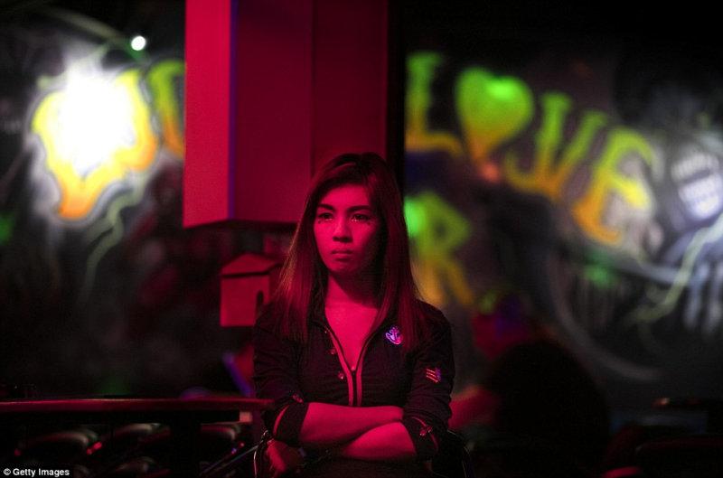 Девушка ждет посетителей у одного из баров в Паттайе.