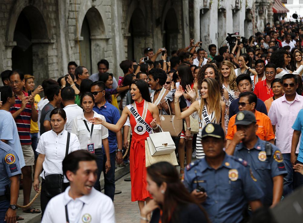 Филиппинские жители приветствуют кандидаток Мисс Вселенная в городе Виган, Филиппины.
