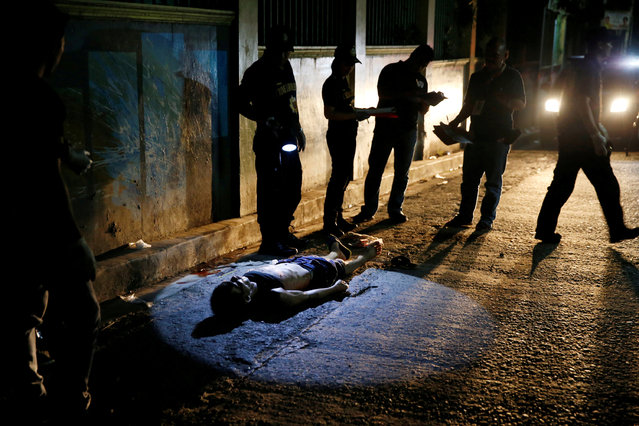 Police investigate the body of Herman Cunanan, whom police said was killed by men riding in two moto