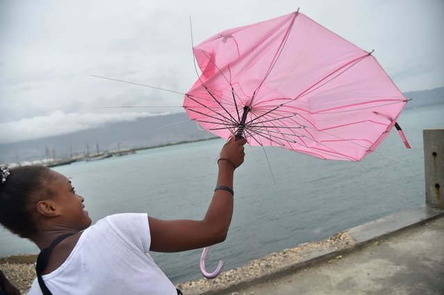 A girl tries to repair her umbrella that was broken by the wind, in the commune of Cite Soleil, in t