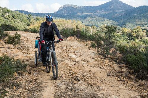 на велосипеде по каменистой горной дороге с прицепом Thule и велокреслом и ребенком