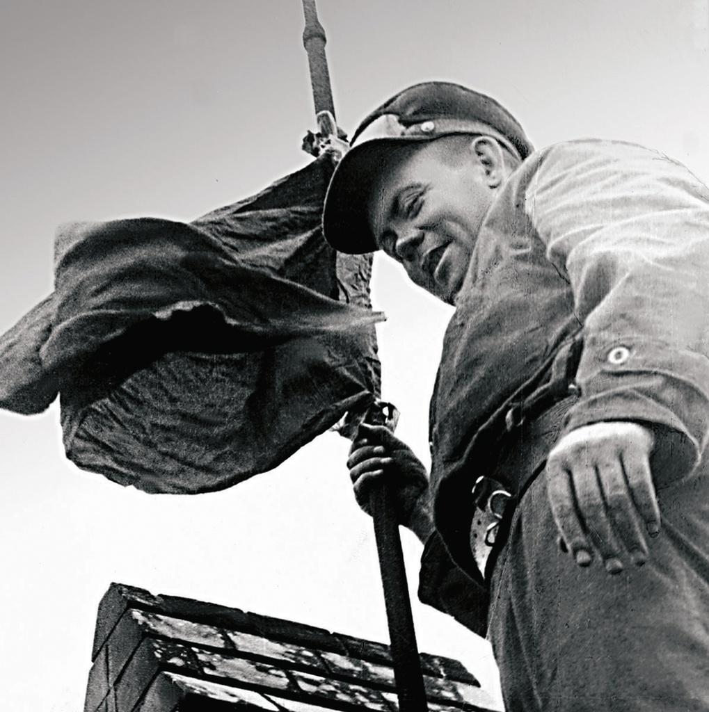 Начальник политотдела 44-й гвардейской танковой бригады Помазнев водружает красный флаг на уцелевшем здании