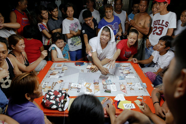 Friends play cards during a wake outside the home of Florjohn P. Cruz who was killed in a police dru