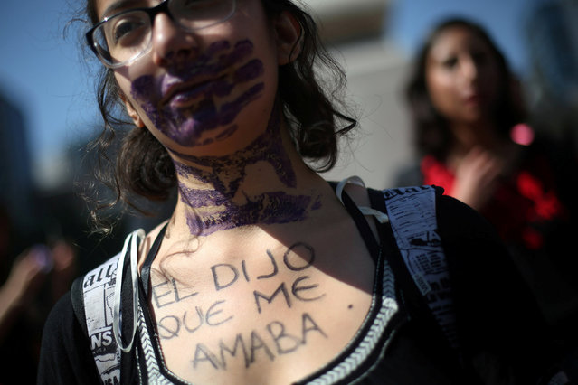 An activist takes part in a protest against violence against women, and of the murder of a 16-year-o