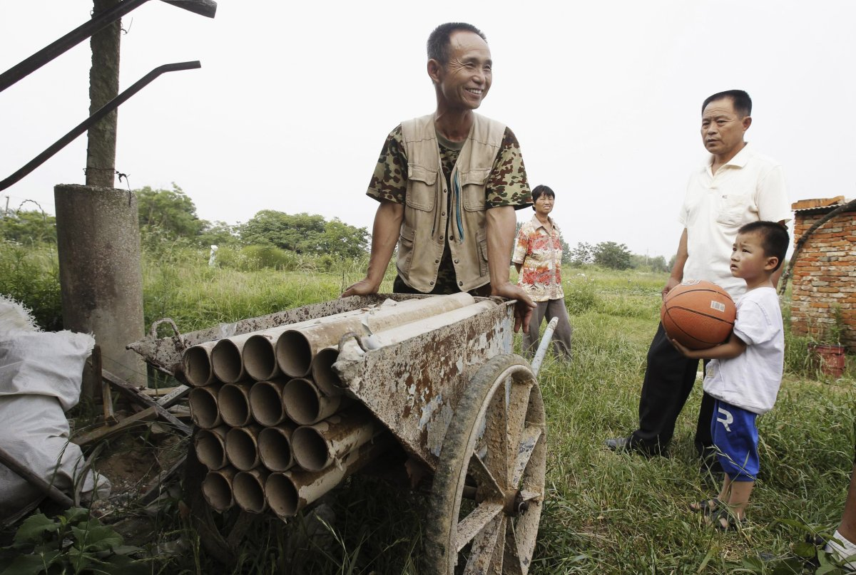 24. Китайский крестьянин Ян Юдэ толкает самодельную пушку на своих владениях на окраине Уханя.