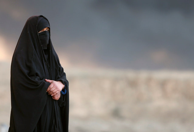 A woman returns to her village after it was liberated from Islamic State militants, south of Mosul i