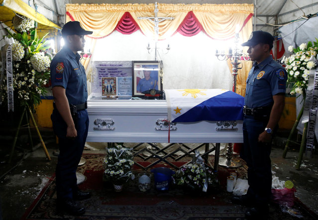 Policemen stand guard in front of the flag-draped coffin of fellow police officer Rancel Cruz, who p