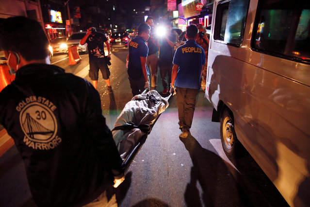 The body of a man killed by unknown gunmen is taken away in Manila, Philippines early October 18, 20