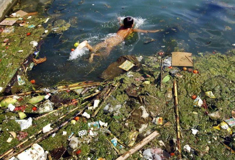 17. Ребёнок плавает в грязном водоеме, Пингба, Китай