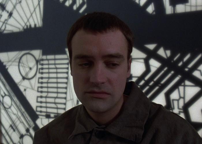 Некий мужчина просыпается в комнате с люками на потолке, полу и стенах. Перебравшись через один из н