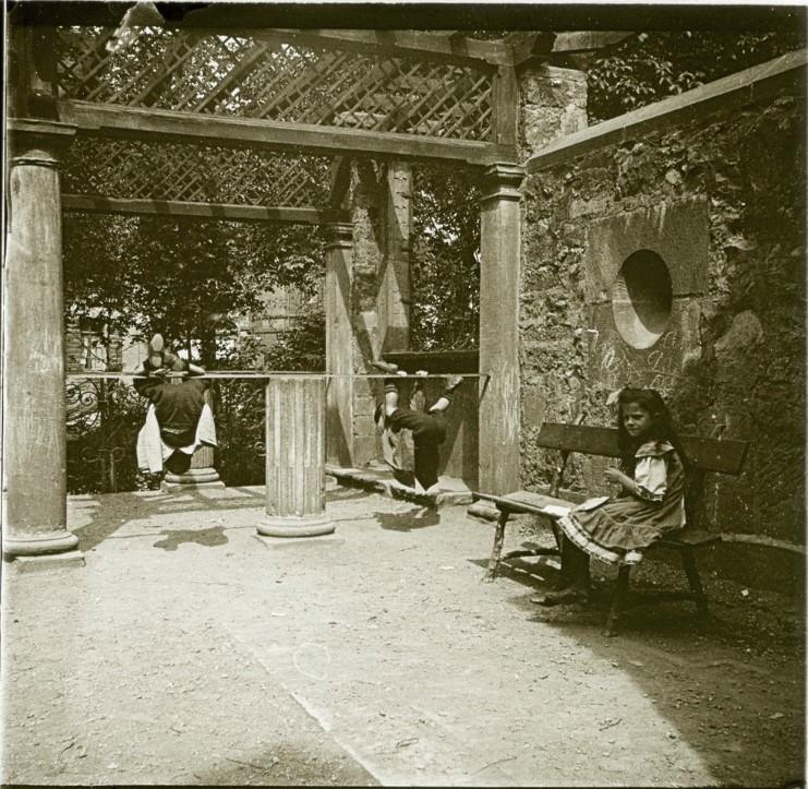 1907. Мальчишки висящие вверх ногами и девочка на скамейке в бывшей монастырской церкви. Германия. Фрайбург
